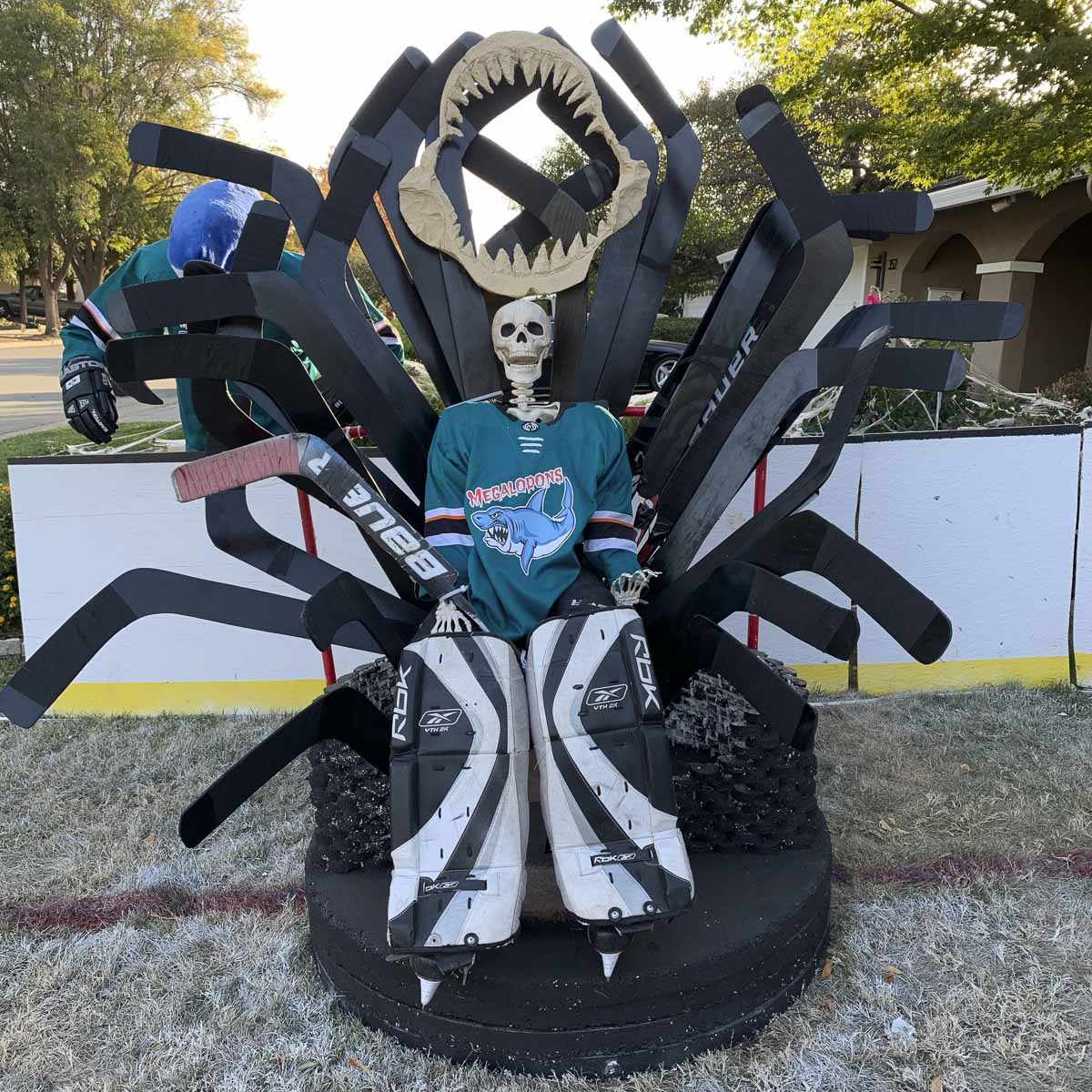 Megalodon goalie #31 Bones (ancestor of SJ Sharks goalie Jones) sitting on a throne made of goalie sticks and hockey pucks inspired by San Jose Sharks Game of Jones bobblehead giveaway.