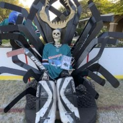 "Megalodon goalie #31 Bones (ancestor of SJ Sharks goalie Jones) sitting on a throne made of goalie sticks and hockey pucks inspired by San Jose Sharks Game of Jones bobblehead giveaway.  He is holding a ""This is Sharks Territory"" sign."