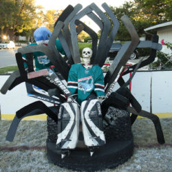 Megalodon goalie Bones (ancestor of SJ Sharks goalie Jones) sitting on a throne made of goalie sticks and hockey pucks inspired by San Jose Sharks Game of Jones bobblehead giveaway.