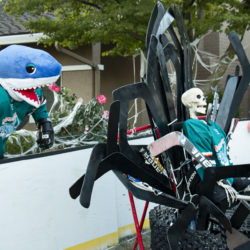 Megalodon goaltender #31 Bones (ancestor of Jones) reigns on his hockey stick and puck throne while Megalodonnie (ancestor of SJ Sharkie) and a little ghost spectator watch this Halloween hockey game.