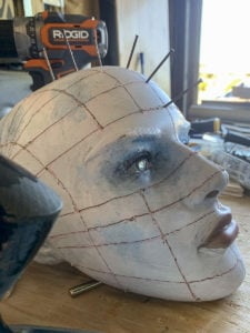 Hammering large nails into predrilled holes in a mannequin head in order to create Pinhead from the Hellraiser movies.