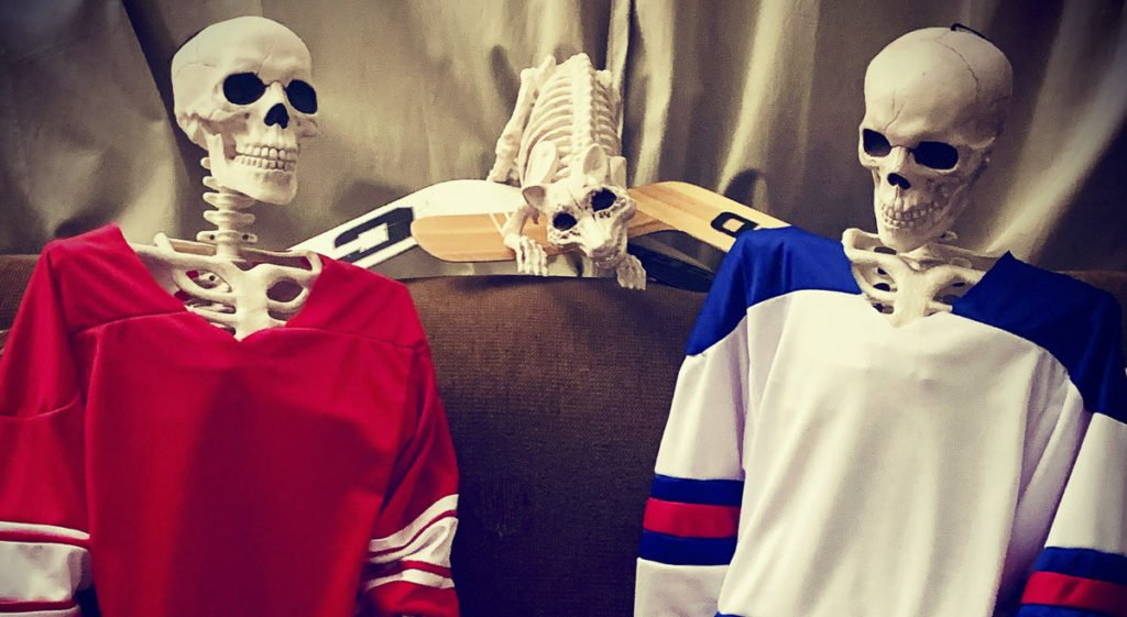 Three plastics skeletons on a sofa, one in an unfinished Soviet hockey jersey, another in an unfinished USA hockey jersey and a raccoon biting on two goalie sticks.