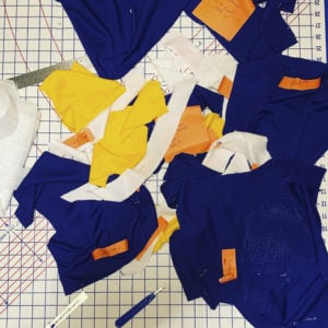 A deconstructed hockey jersey that had been ripped apart at the seams and scattered on a cutting mat.