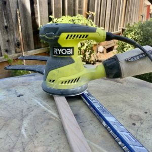 Using a Ryobi random orbital sander to remove paint from an old hockey stick.
