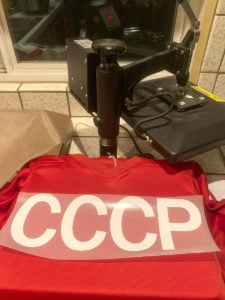 Using a heat press to affix heat transfer vinyl to a jersey to create a costume Team USSR hockey jersey for Halloween.