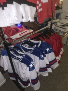 Garment rack full of partially finished Team USA and USSR jerseys, shorts, and socks for the Halloween Miracle on Ice hockey game.