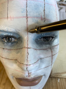 Using a wood burning tool to carve lines in a mannequin head in order to create Pinhead from the Hellraiser movies.