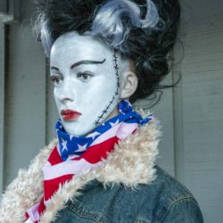 The Bride of Frankenstein in a denim jacket and a flag scarf looks in support of Team USA the Halloween Miracle on Ice hockey game.