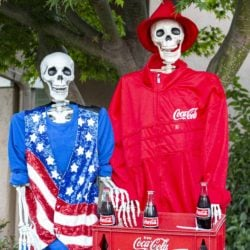 A very patriotic team USA skeleton fan in a star-spangled vest enjoys the bottle of Coca Cola he purchased from a vendor at the area refreshment stand.