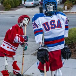 USA skeleton McClanahan looking proud and USSR skeleton Pervukhin looking discouraged after team USA wins in the Halloween Miracle on Ice hockey game.