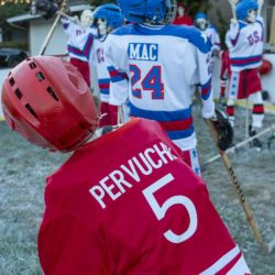 USSR skeleton Pervukhin leans heavily on his hockey stick watching the Team USA skeletons celebrate after the Halloween Miracle on Ice hockey game.
