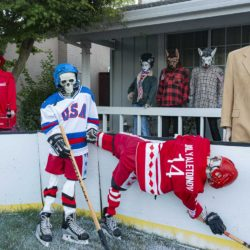 "USSR skeleton Bilyaletdinov hangs off the boards after a crash with USA skeleton Ramsey as Team USA Coach Herb ""Hellraiser"" Brooks and the USA fans (the Bride of Frankenstein, two werewolves, a star-spangled skeleton, and a skeleton Coca Cola vendor) watch the action in the Halloween Miracle on Ice hockey game."