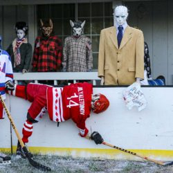 "USSR skeleton Bilyaletdinov hangs off the boards after a crash with USA skeleton Ramsey as Team USA Coach Herb ""Hellraiser"" Brooks and the USA fans (the Bride of Frankenstein and two werewolves) watch the action in the Halloween Miracle on Ice hockey game."