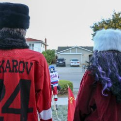 Traditional Halloween characters (a witch in a fancy faux-fur hat and Michael Meyers in a warm faux-fur hat and a Makarov jersey) cheer on their seemingly invincible Soviet team in the Halloween Miracle on Ice hockey game.