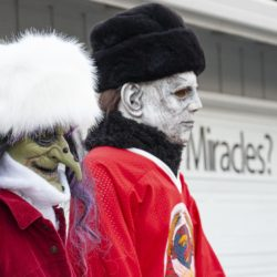Traditional scary Halloween characters (a witch and Michael Meyers) in faux-fur hats cheer on the Soviets in the Halloween Miracle on Ice hockey game.