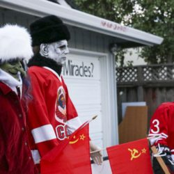 Outdoor Halloween display showing two traditional scary characters (a witch and Michael Meyers) in faux-fur hats and waving the Soviet flag while they cheer on the skeleton team captain (Mikhailov) and the rest of the Soviet team playing in the Halloween version of the 1980 Miracle on Ice hockey game.