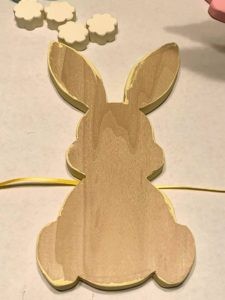 Back side of wood bunny shape on top of a piece of ribbon before adding glue.