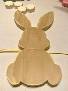 Back side of wood bunny shape on top of a piece of ribbon with a strip of hot glue on back.