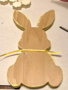 Back side of wood bunny shape on top of a piece of ribbon. Strands of ribbon have been criss-crossed across the back in the hot glue.
