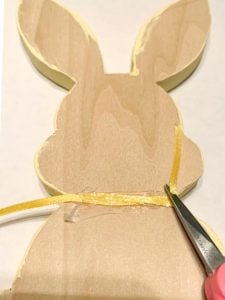 Back side of wood bunny shape with ribbon wrapped around neck and glued in the back. Using scissors to snip off the excess ribbon.