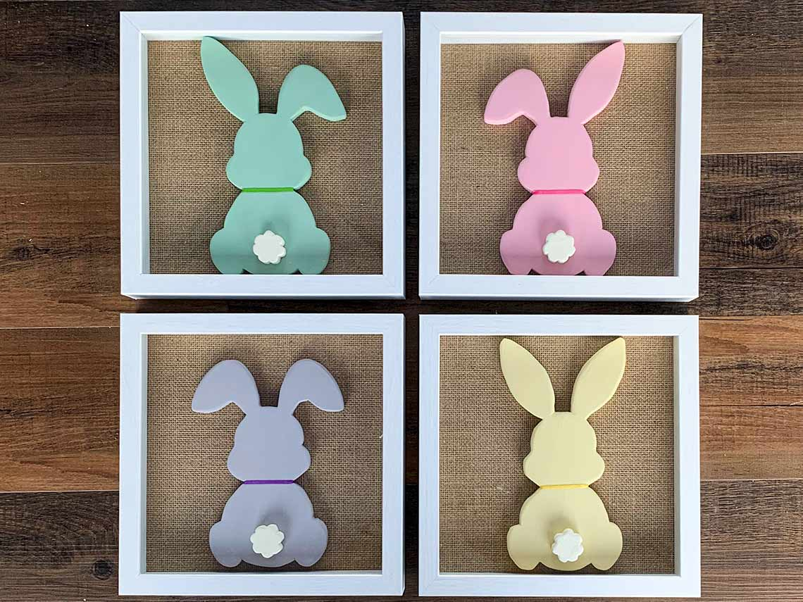 Series of four wood bunny silhouettes each on a burlap mat in a shadowbox frame. Bunnies are painted with chalk paint and have a ribbon around their necks and raised tails.