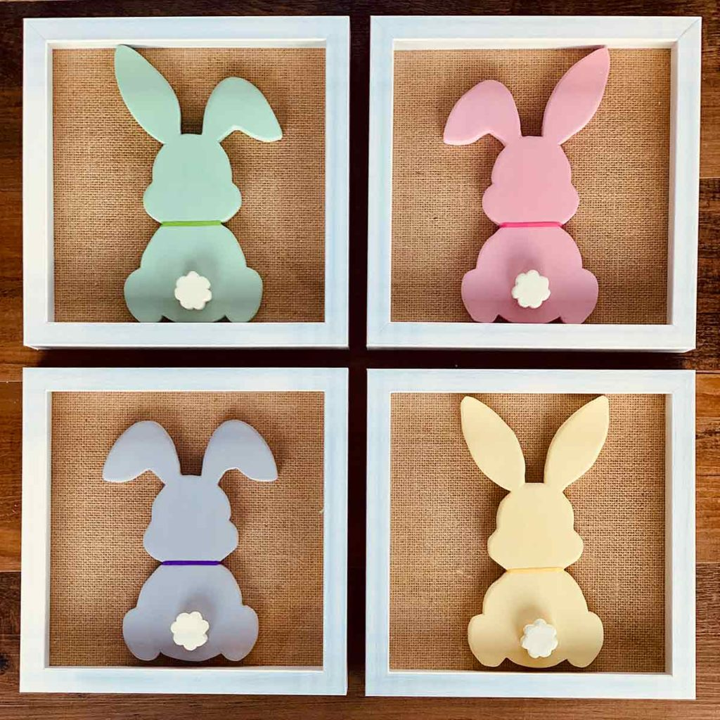 Series of four wood bunny silhouettes each on a burlap mat in a shadowbox frame arranged in a square. Bunnies are painted with chalk paint and have a ribbon around their necks and raised tails.