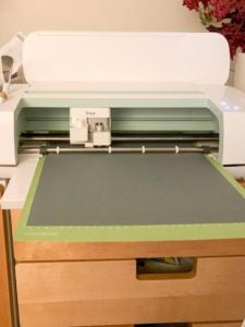 Cricut maker cutting a shape out of grey cardstock. This template was used to later cut the wood on a scroll saw.