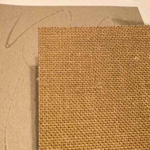 Hot glue on chipboard and a piece of paper-backed burlap. The burlap will be glued to the chipboard.