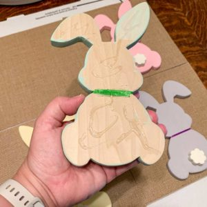 Hot glue applied to back of painted wood bunny. Bunny will be glued down onto the burlap.