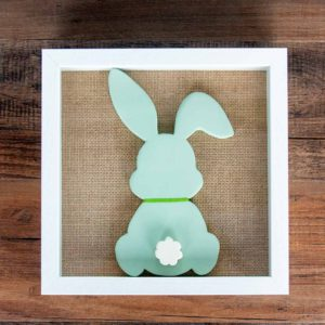 Wood bunny silhouette on a burlap mat in a shadowbox frame. Bunny is painted with green chalk paint, has a green ribbon around its neck, and features a white raised tail.