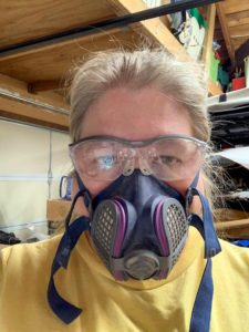 Woman wearing personal protective equipment (respirator mask and safety glasses) to protect from dust while using the scroll saw or sanding.