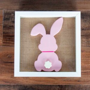 Wood bunny silhouette on a burlap mat in a shadowbox frame. Bunny is painted with pink chalk paint, has a pink ribbon around its neck, and features a white raised tail.
