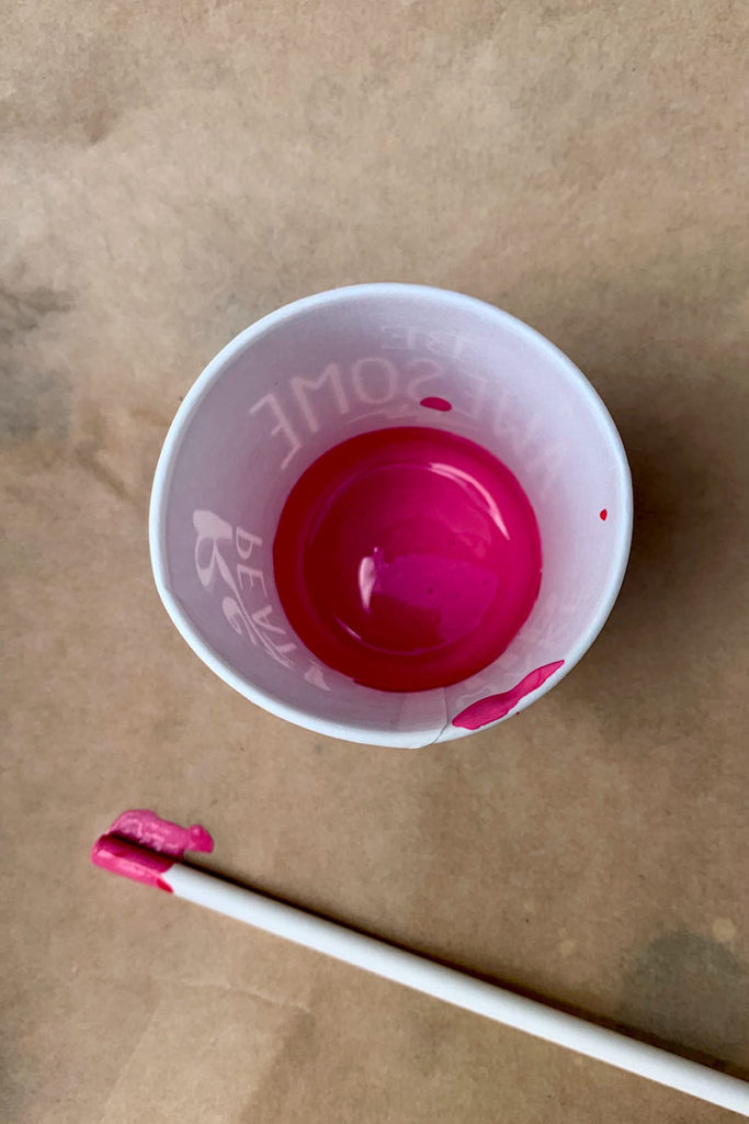 Cup of blended, well-mixed Magenta and Ivory pouring paint.