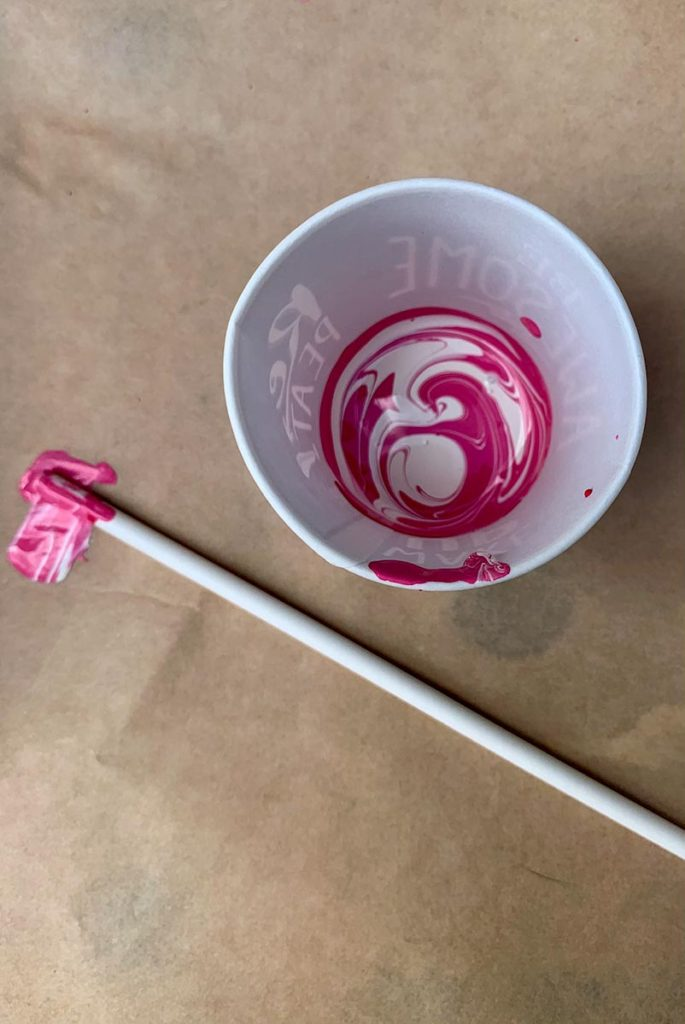 Pink and Ivory pouring paint swirled in a cup.