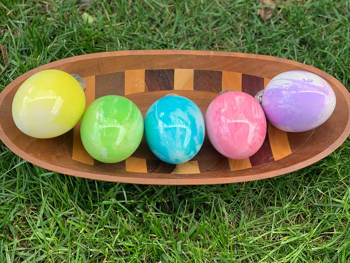 Five Pouring Paint Easter Eggs in a wooden bowl showing color and design variations