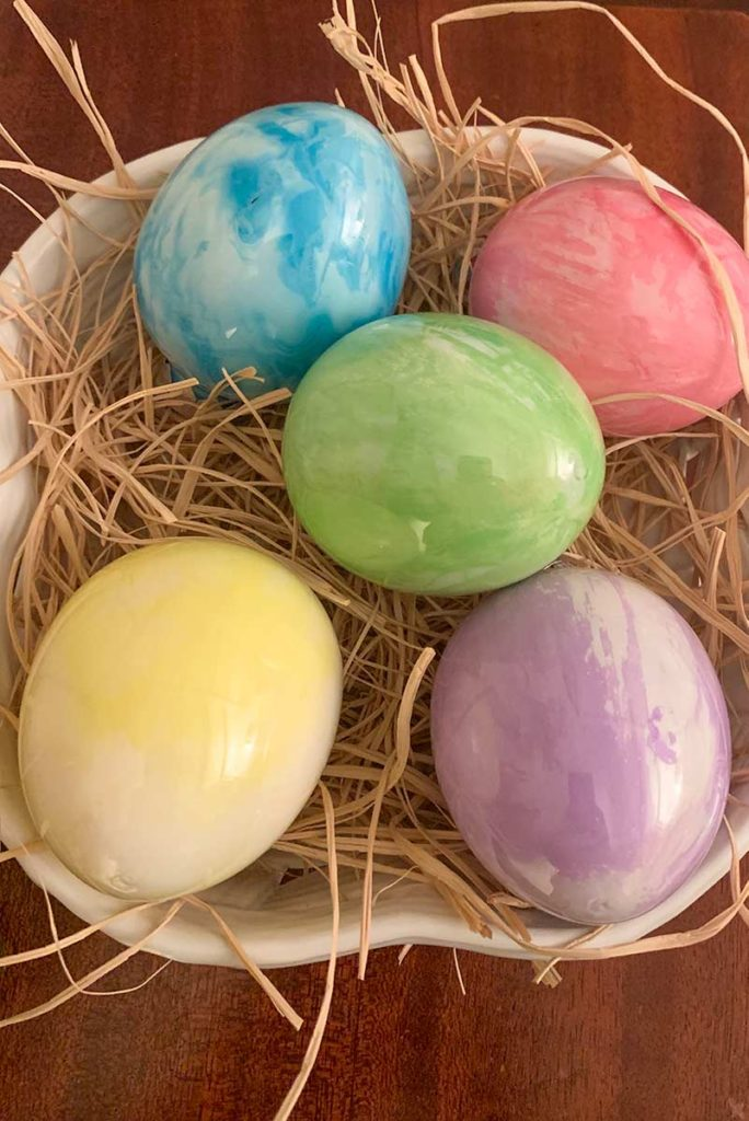 Five Pouring Paint Easter Eggs in a basket showing color and design variations