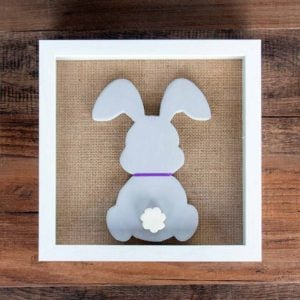 Wood bunny silhouette on a burlap mat in a shadowbox frame. Bunny is painted with purple chalk paint, has a purple ribbon around its neck, and features a white raised tail.