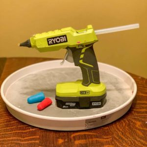 Ryobi cordless hot glue gun with a stick of glue and two silicone finger protectors
