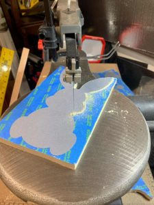 Cutting a bunny on a scroll saw by following the cardstock template glued to the painter's tape on top of the piece of poplar wood.