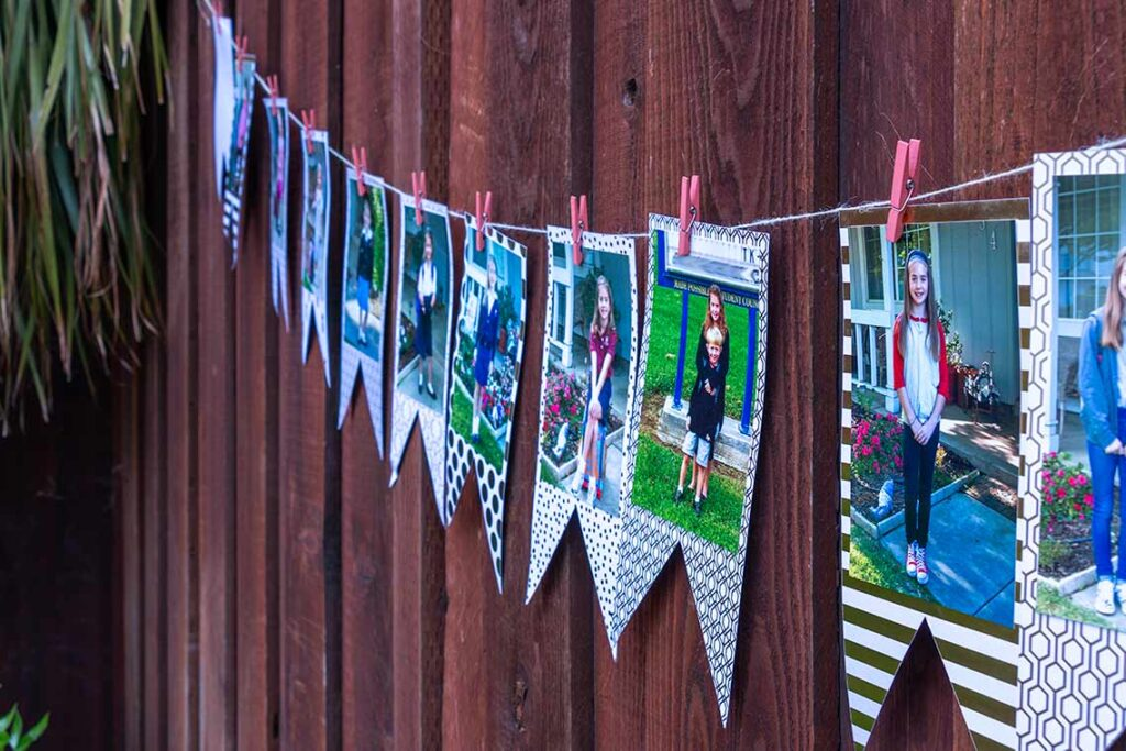 Side view of graduation banner showcasing 1st day of school pictures mounted on white and gold cardstock hanging from twine by mini clothespins