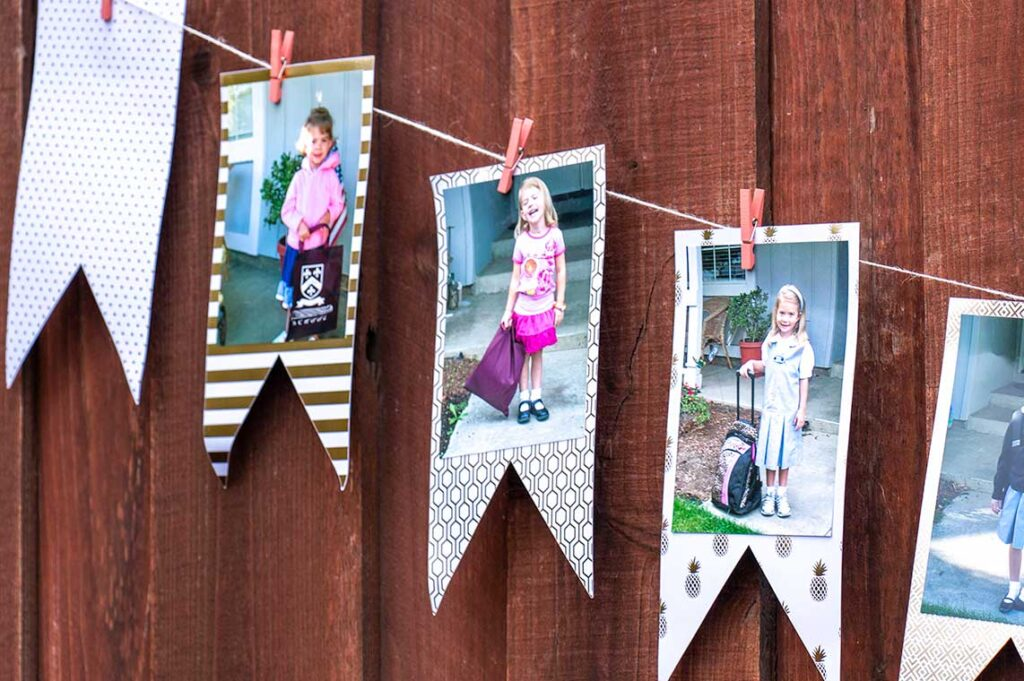 Closeup of graduation banner showcasing 1st day of school pictures mounted on white and gold cardstock hanging from twine by mini clothespins