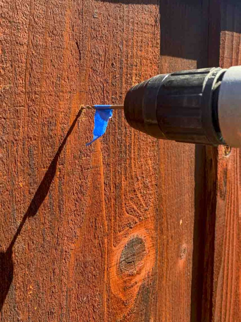 Drilling a hole in the fence for the gutter garden installation. Drill bit has a piece of painters tape to indicate when to stop drilling.