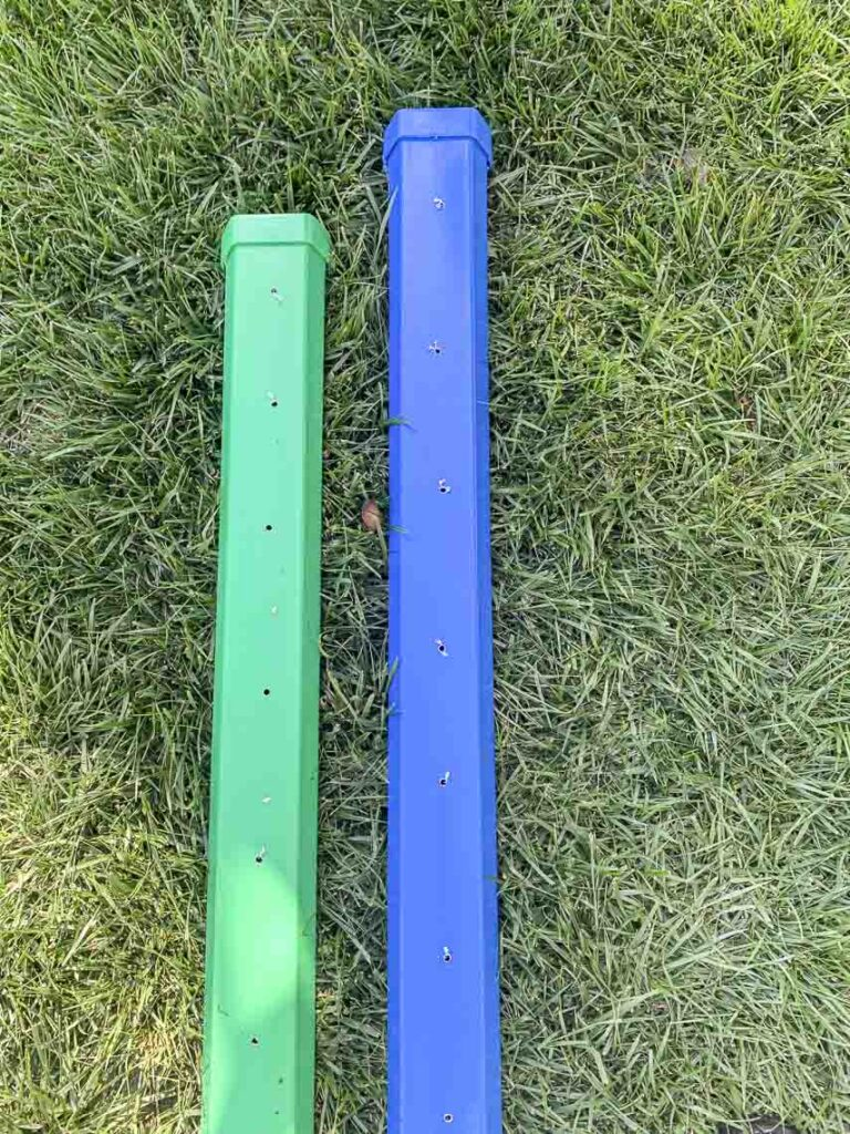 Two vinyl gutters painted green and blue with holes drilled in the bottom to allow for gutter garden drainage.