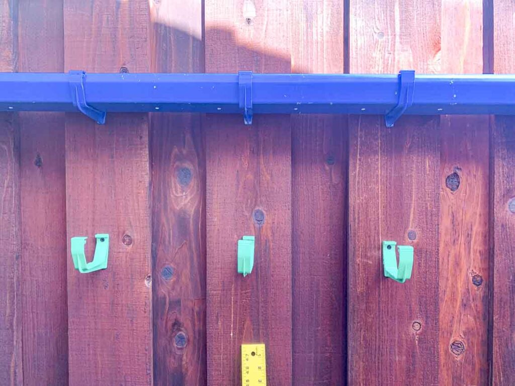 One gutter garden mounted on a fence and a series of hanging brackets screwed into the fence awaiting addition of the second planter.
