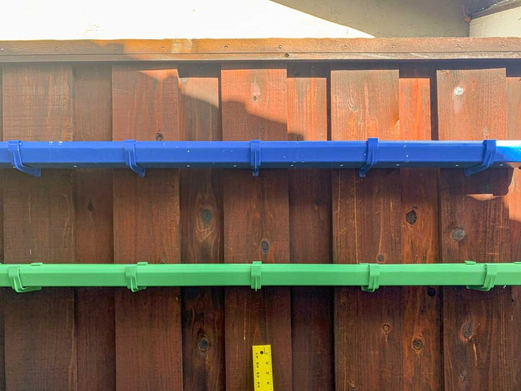 Two empty gutter planters mounted on the fence prior to adding the plants. Image also shows the scratches in the paint from applying the mounting hooks.