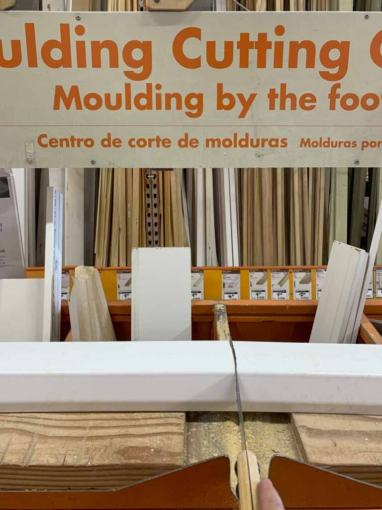 Using a hand saw to cut the 10 foot piece of gutter in half at the moulding cutting station in Home Depot.