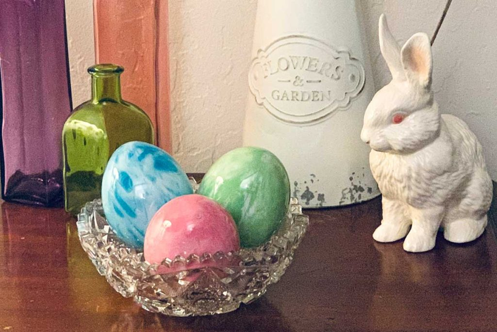 Pouring Paint Easter Eggs made from Christmas ornaments surrounded by spring decor