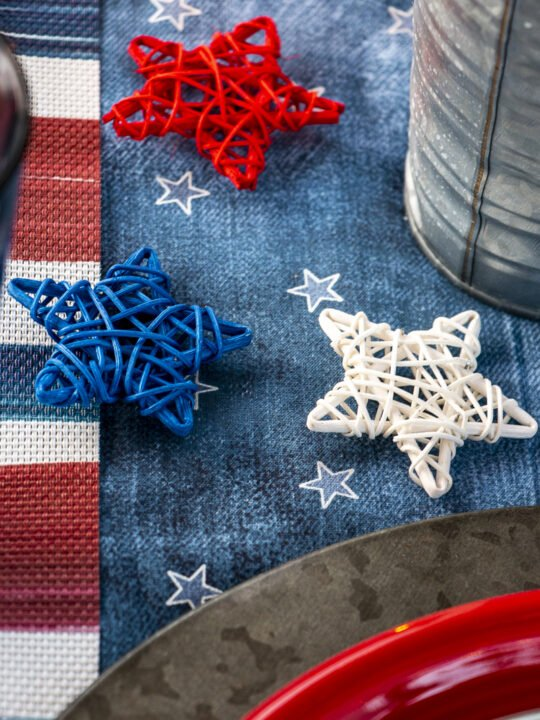 Red, white, and blue rattan stars on a denim table runner