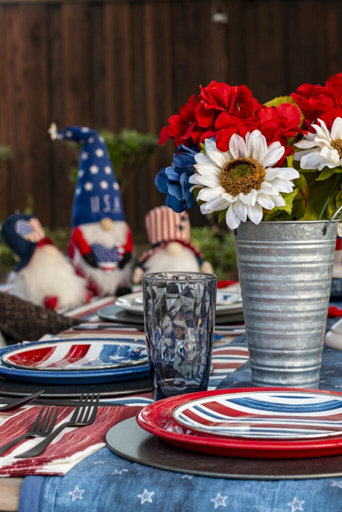 4th of July table setting (stars and stripes enamel salad plates; red, white, & blue dinner plates; blue drinking glasses; and patriotic flowers in tin vases). Three festive gnomes on a table in the background.