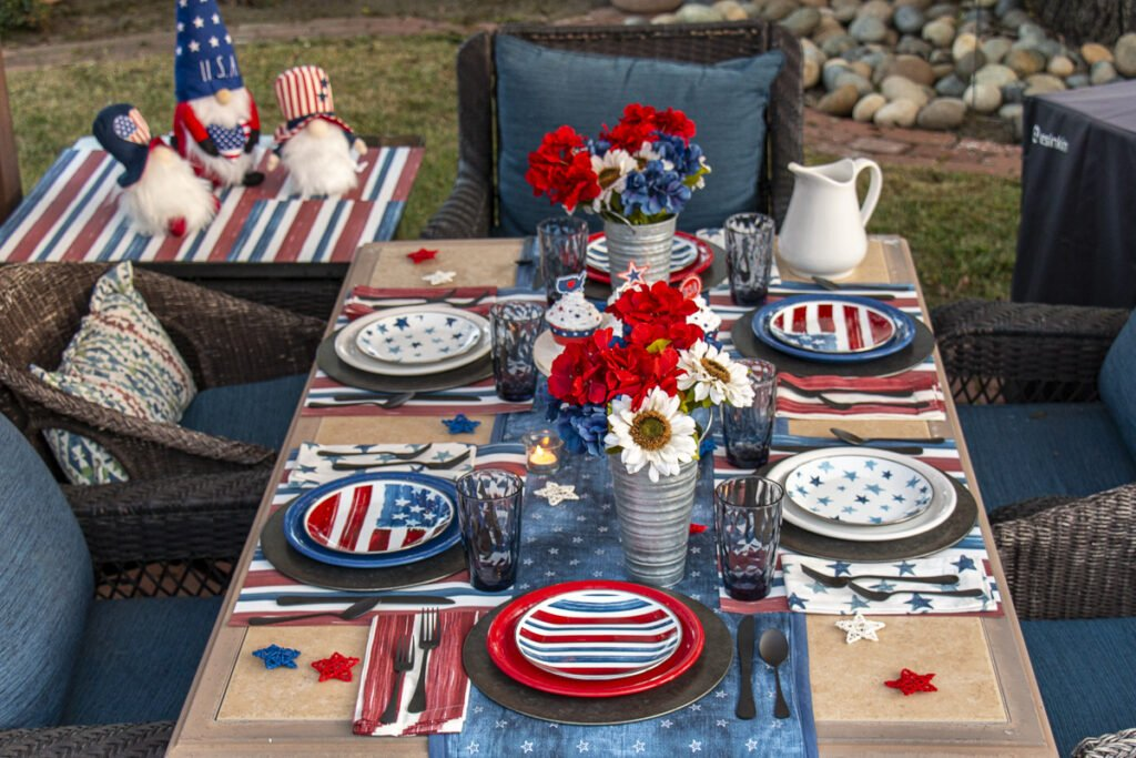 Overhead view of red, white, and blue tablescape covered with patriotic decor including Potty Barn stars and stripes plates and linens, flowers in tin vases, blue glasses, and a white pitcher.